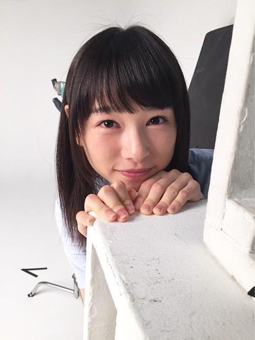 机の角からひょこっと顔を出す笑顔の桜井日奈子