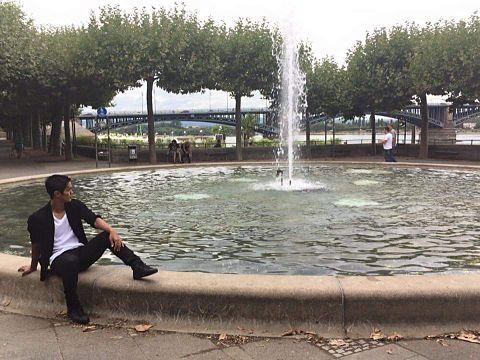 大きな噴水の淵に腰掛ける武藤選手