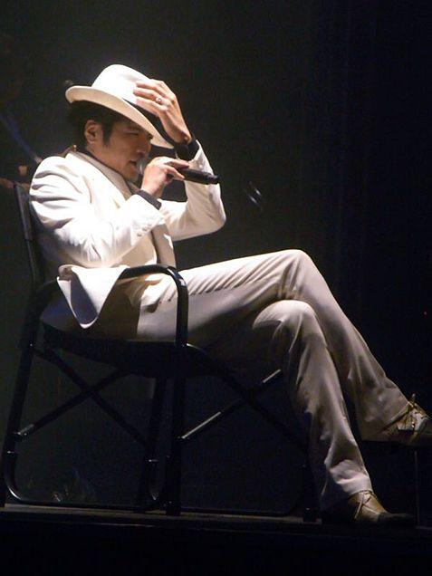 ハットを手で押さえながら足を組んで座る吉川晃司