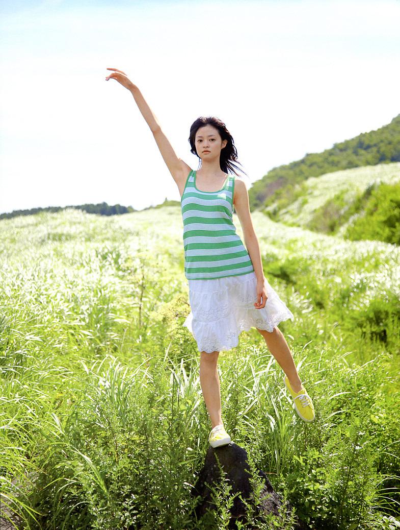 ボーダーのシャツを着て岩の上に立っている小林涼子の画像