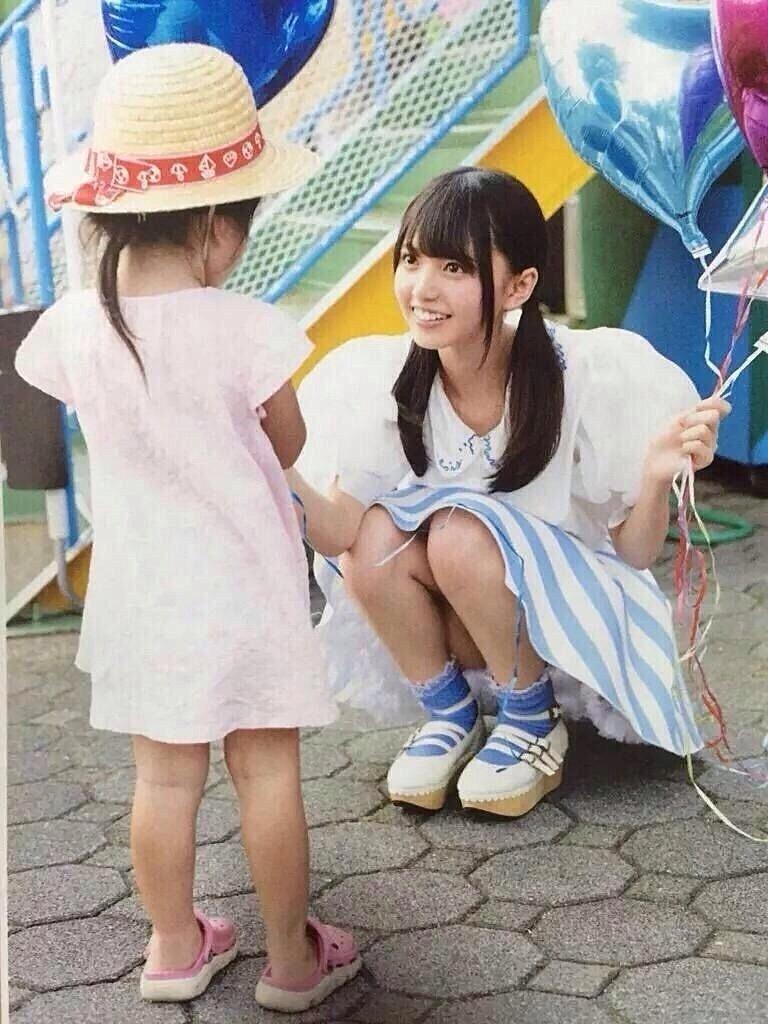 小さな女の子に目線を合わせて風船を手渡す齋藤飛鳥