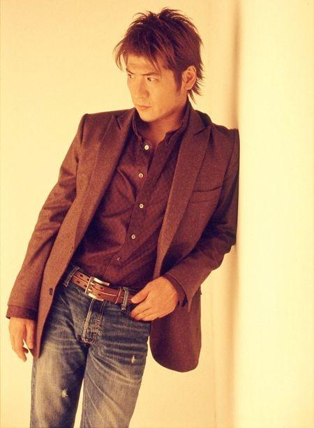 壁にもたれかかっている吉川晃司