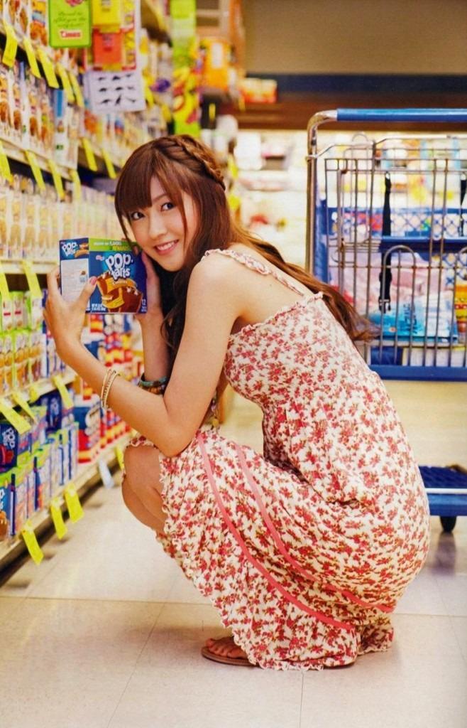 商品を座って手に取って笑顔の熊井友理奈