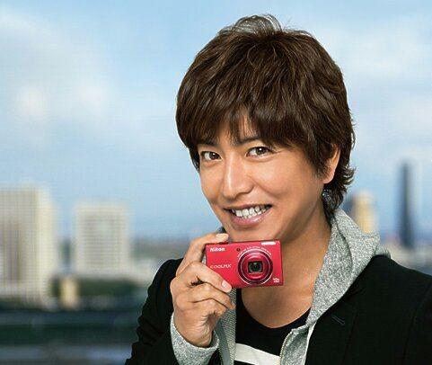カメラを持ってニコッと白い歯を見せて笑う木村拓哉